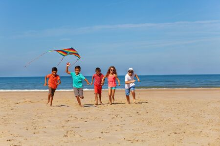Many kids run on the beach with color kite