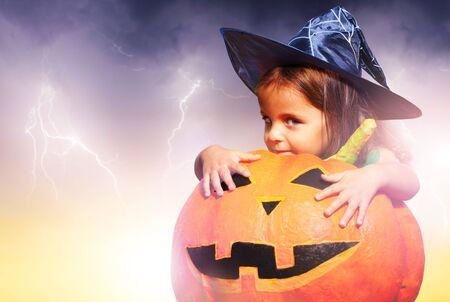 Girl expression in Halloween costume hug pumpkin