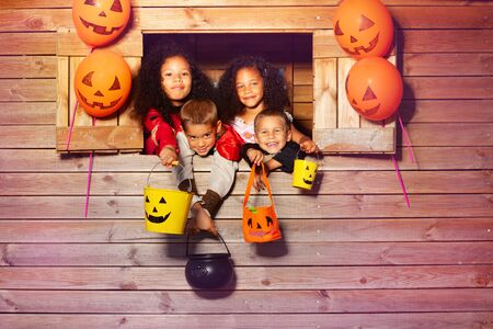 Group of kids with Halloween buckets in treehouse
