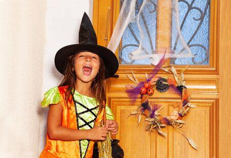 Girl in witch costume knock the door on Halloween 免版税图像