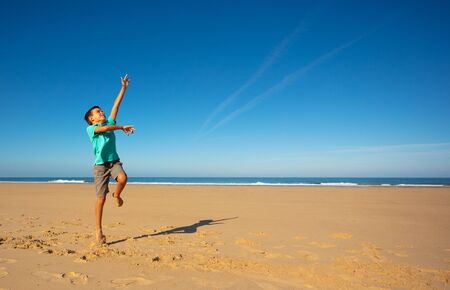 Happy boy in blue shirt jump high on the sand beach pulling hand up near the sea