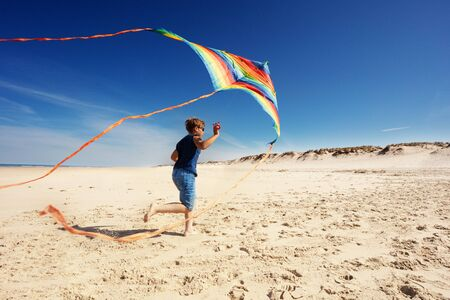 Boy run on the sand beach holding colorful rainbow stripped kite view from behind