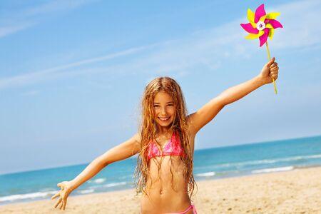 Happy girl smile in bikini on beach with pinwheel Standard-Bild
