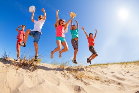 Happy group of children jump down from sand dune view from bellow lifting hands holding hats in casual clothes