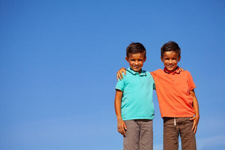 Close portrait of two boys hug over blue sky