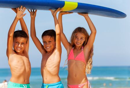 Three smiling kids boys and girl carry surfboard