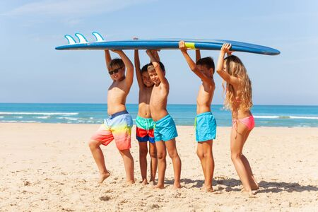 Kids portrait carry surfboard on the beach