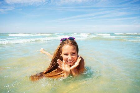 Cute girl play in waves holding palms near face