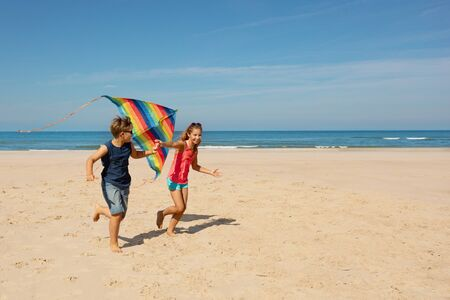 Two kids brother and sister on the sand beach run with colorful stripped rainbow color kite in casual summer clothes