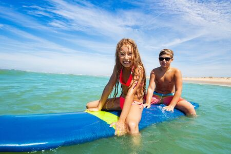 Boy and smiling girl sit swimming on surf board