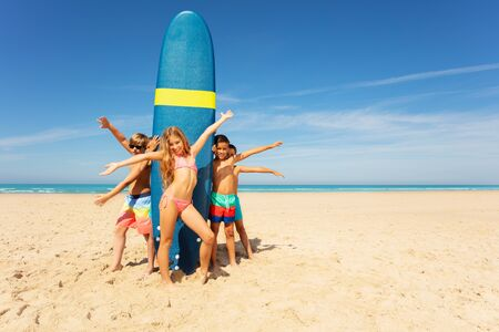 Group of kids stand waving hands near surfboard Imagens