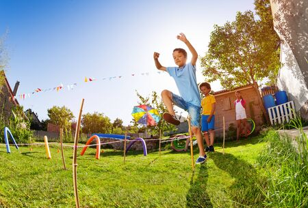 Boy jumping over string in competition game