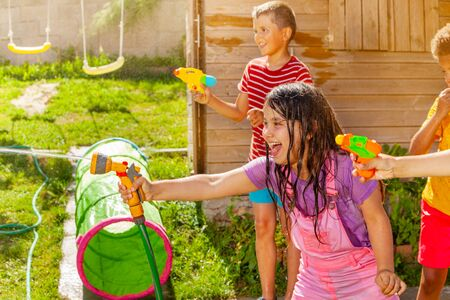 Summer fun - girl shoot water gun in group of kids Stock fotó