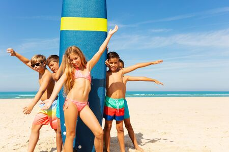 Group of kids stand near surfboard on the beach