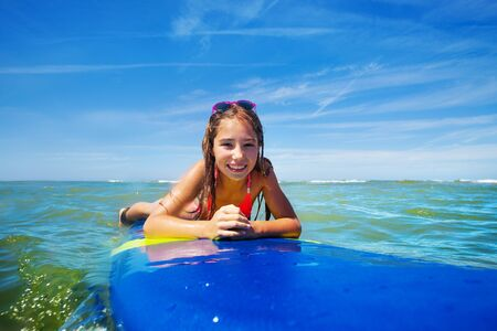 Happy surfer girl lay on surfboard wait for wave