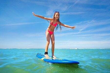 Little girl surf sea waves standing on surfboard