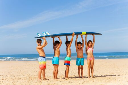 Kids on the beach boys and girls hold surfboard with sea on background