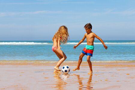 Two kids boy and girl play soccer football ball on sand beach near the water edge