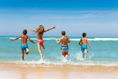 Group of kids run into waves with little girl jump in water having wide spread hands