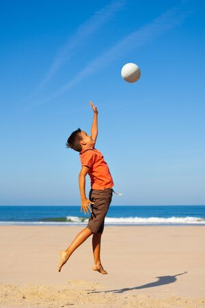 Happy little hands boy play volleyball on the beach hitting the ball with sea on background Standard-Bild