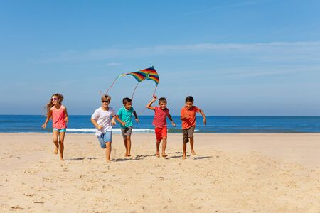 Grupo de niños con cometa colorida en una playa