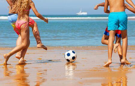 Primer plano de las piernas de los niños jugar al fútbol en la playa del mar