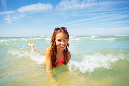 Happy girl lay in the sea waves smiling on a beach