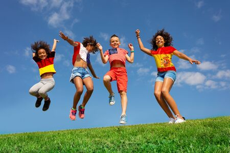 Many kids in different national flag shirts jump Stockfoto