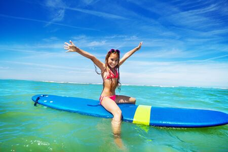 Beautiful little girl surfer sit on surfboard