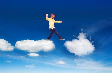 Little boy walking from one cloud to another Reklamní fotografie