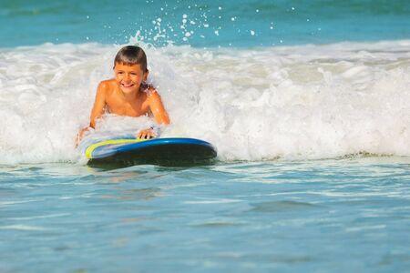 Happy smiling little boy lay on surfboard in sea