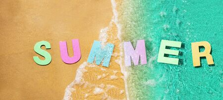 Summer sign made of colorful letters floating in the water near beach sand edge Stock Photo