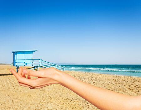 Hand hold between fingers lifeguard tower LA beach