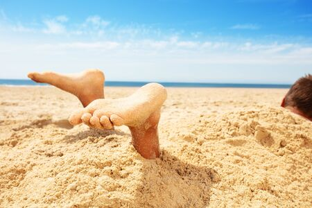 Legs and feet boy covered by sand in a game on sea Stock Photo