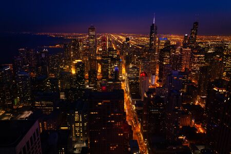 Magnificent night panorama view of streets and tall skyscrapers of Chicago from above