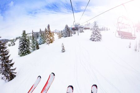 Parts of ski and lift over magnificent snow covered fir forest view on Alpine mountain resort