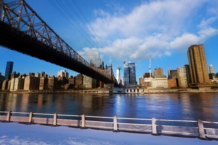 Winter view of Ed Koch Queensboro Bridge over New York buildings across East river from Roosevelt Island, NY, USA