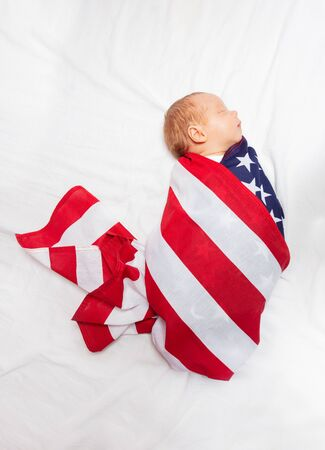 Portrait of little baby infant boy wrapped in USA flag laying on the bed sheet