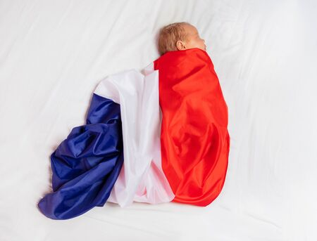 Portrait of little baby infant boy wrapped in national flag of France laying on the bed sheet Stock Photo