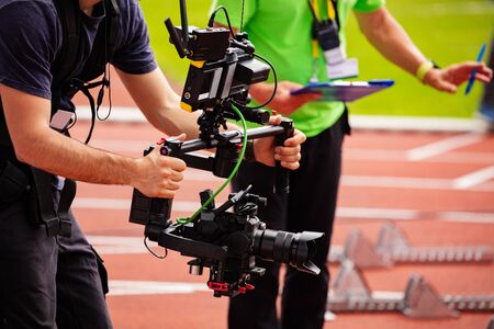Close-up of videographer shooting with camera standing on the track