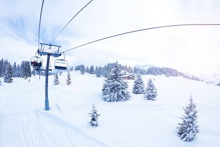 Ski lift over magnificent snow covered fir forest on Alpine mountain resort