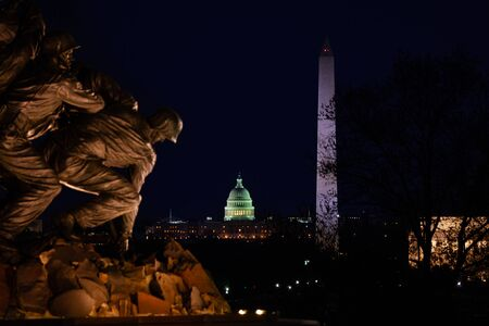 ARLINGTON, VA - APRIL 27, 2018: Washington Monument and US Capitol behind close-up of Memorial in Washington during night. The Memorial to honor the Marines who have died defending the US since 1775. Editorial