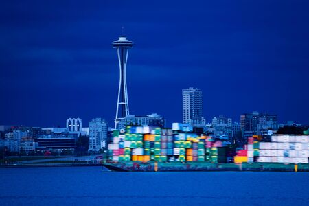 Cargo ship with containers pass Seattle Elliot harbor over Space needle and downtown panorama, Washington, USA