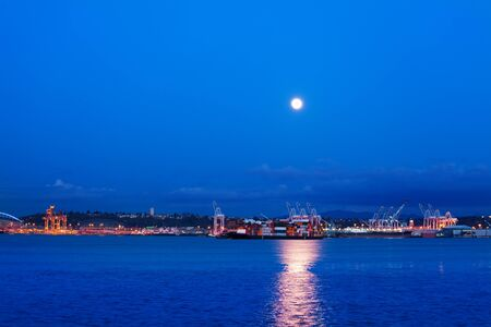 Big lune with trail on water of Elliot bay over Seattle port night view, WA, USA