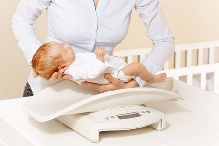 Mother put little newborn baby infant boy to the scale to measure body weight Archivio Fotografico
