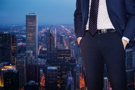 Businessman in suit with tie standing near the window of Chicago downtown, Illinois, USA Stock Photo