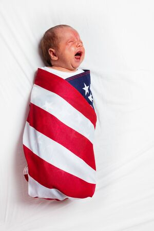 Portrait of little crying baby infant boy wrapped in US American flag laying on the bed sheet