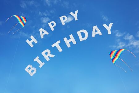 Happy birthday sign text made of clouds letters over clear day blue sky with colorful flying kites