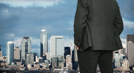 Back of businessman in suit standing near the window of Seattle downtown Washington, USA during day Stock Photo