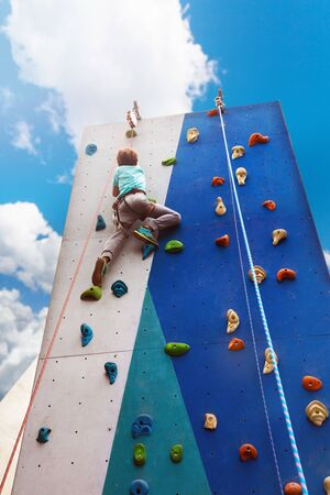 Little child boy on rock climb high on the wall in the sport park outside over blue sky Stock Photo